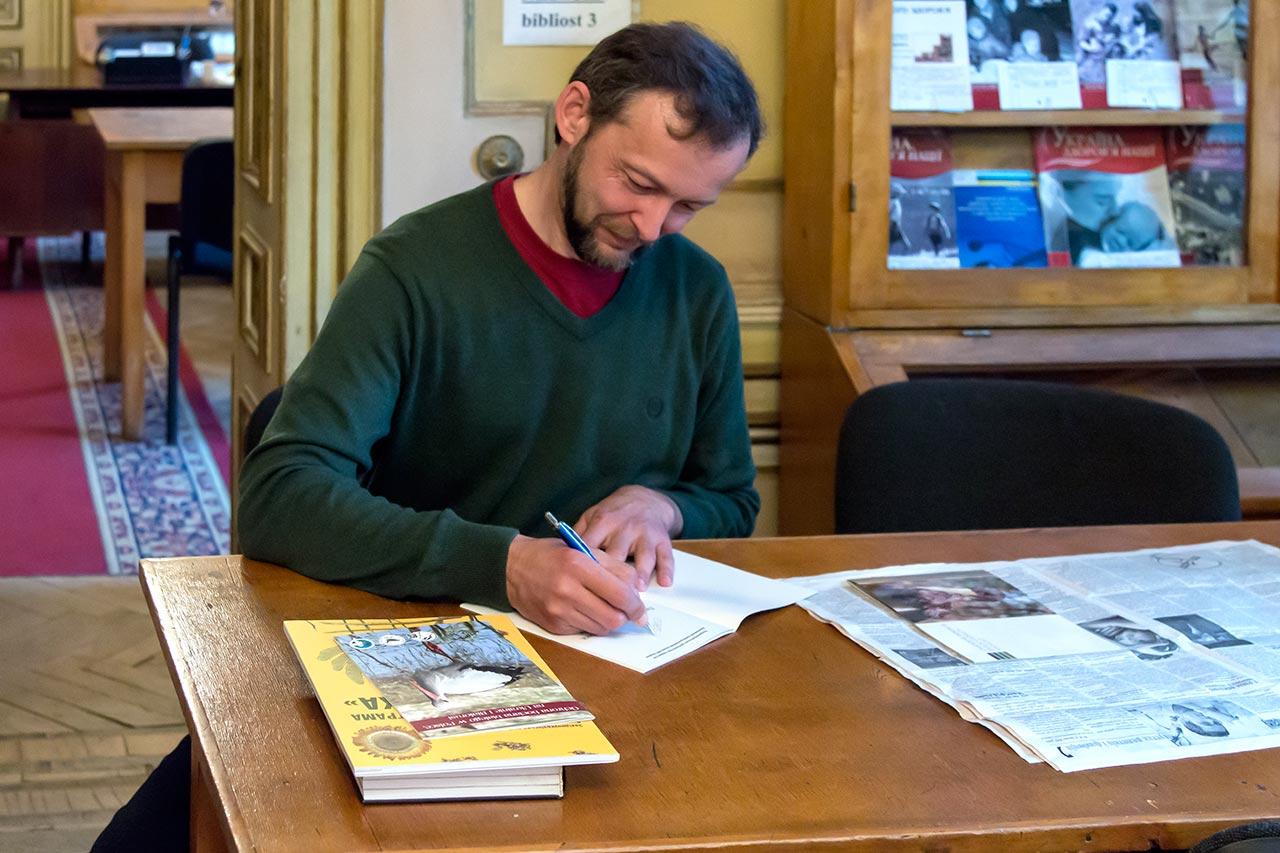 Кандидат біологічних наук Андрій Бокотей підписує книги